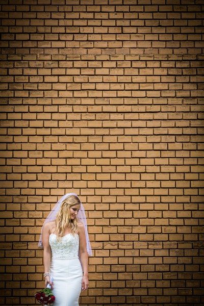 Esküvőfotózás menyasszony téglafal előtt -pixLX